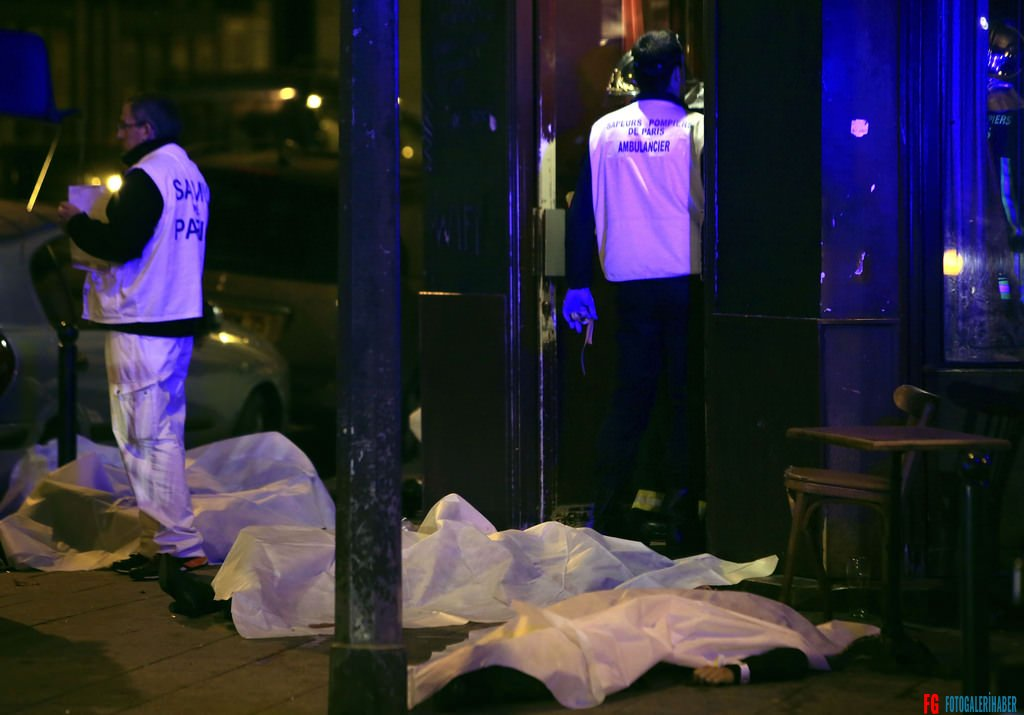 Victims lay on the pavement in a Paris restaurant, Friday, Nov. 13, 2015. Two police officials say at least 11 people have been killed in shootouts and other violence around Paris. Police have reported shootouts in at least two restaurants in Paris. At least two explosions have been heard near the Stade de France stadium, and French media is reporting of a hostage-taking in the capital. (AP Photo/Thibault Camus)