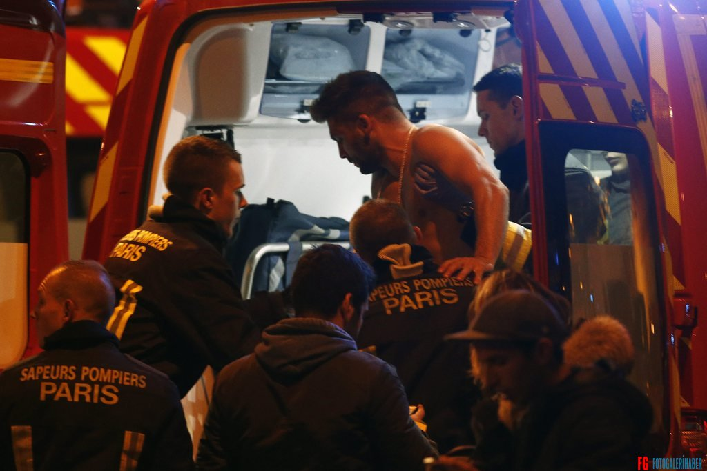 epa05023806 A wounded man is put into a fireman truck next to the Stade de France where three bombs exploded in the North of Paris, France, late 13 November 2015. At least 18 people were reported dead in attacks, French media report, citing police in the capital.  EPA/ETIENNE LAURENT