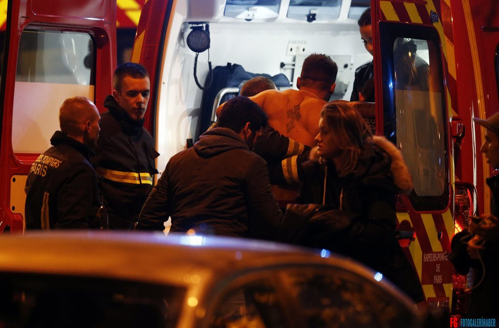 epa05023808 A wounded man is put into a fireman truck next to the Stade de France where three bombs exploded in the North of Paris, France, late 13 November 2015. At least 18 people were reported dead in attacks, French media report, citing police in the capital.  EPA/ETIENNE LAURENT