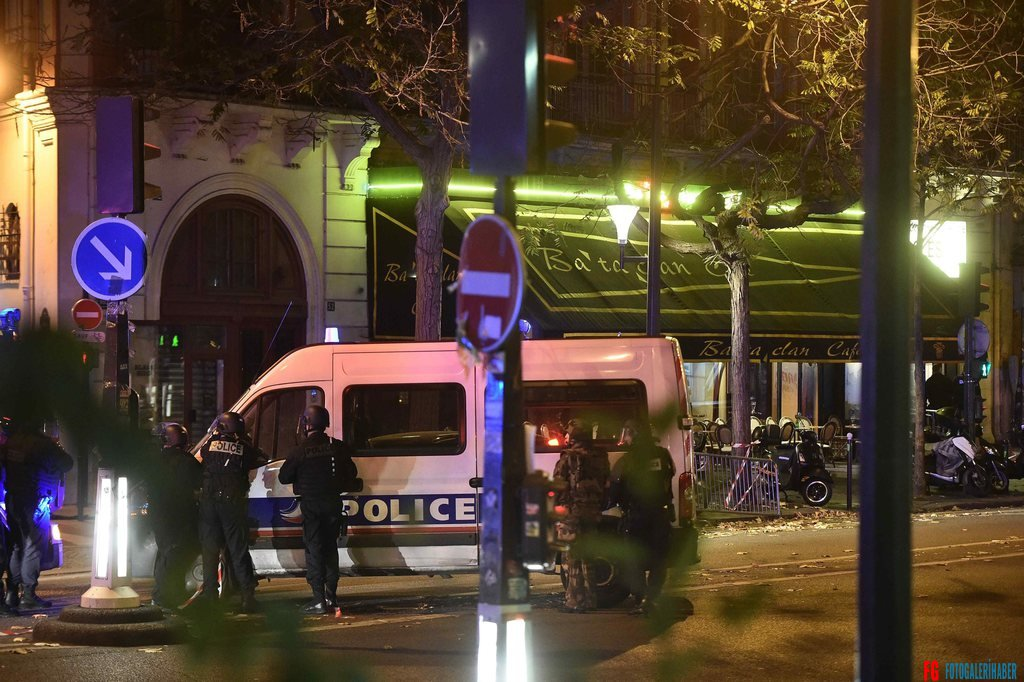 epa05023834 Police officers gather outside the Bataclan concert venue in Paris, France, 13 November 2015, where a gunman has reportedly taken people hostage. At least 26 people have died in attacks in Paris on 13 November after reports of a shootout and explosions near the Stade de France stadium.  EPA/CHRISTOPHE PETIT TESSON