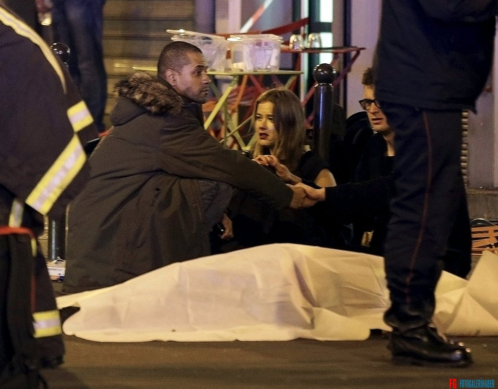 ATTENTION EDITORS - VISUAL COVERAGE OF SCENES OF INJURY OR DEATH  A general view of the scene that shows rescue services personnel working near the covered bodies outside a restaurant following a shooting incident in Paris, France, November 13, 2015.   REUTERS/Philippe Wojazer