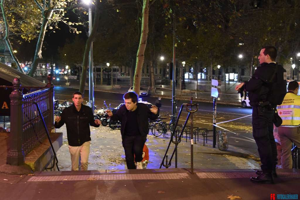 Two men evacuate the Place de la Republique square in Paris as a police officer looks on, after several shootings on November 13, 2015. At least 18 people were killed in several shootings and explosions in Paris today, police said.  AFP PHOTO / DOMINIQUE FAGET
