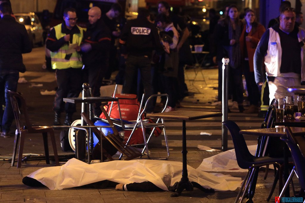 A victim is pictured on the pavement outside a Paris restaurant, Friday, Nov. 13, 2015. Two police officials say at least 11 people have been killed in shootouts and other violence around Paris. Police have reported shootouts in at least two restaurants in Paris. At least two explosions have been heard near the Stade de France stadium, and French media is reporting of a hostage-taking in the capital. (AP Photo/Thibault Camus)