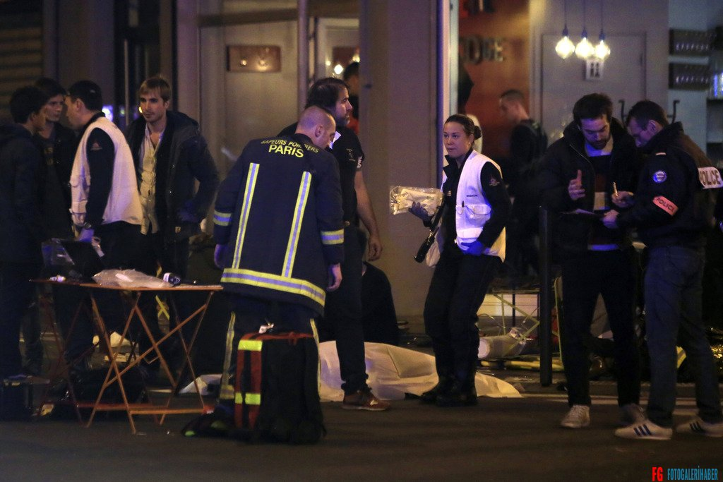 Police officers and rescue workers gather around a victim outside a Paris restaurant, Friday, Nov. 13, 2015. Two police officials say at least 11 people have been killed in shootouts and other violence around Paris. Police have reported shootouts in at least two restaurants in Paris. At least two explosions have been heard near the Stade de France stadium, and French media is reporting of a hostage-taking in the capital. (AP Photo/Thibault Camus)